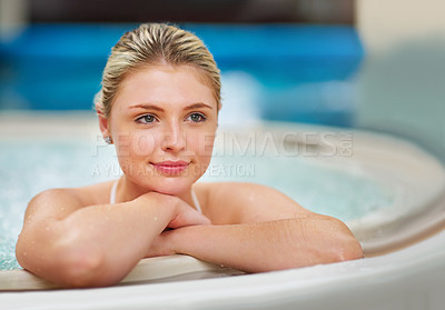Buy stock photo Shot of a thoughtful young woman relaxing in the jacuzzi at a spa