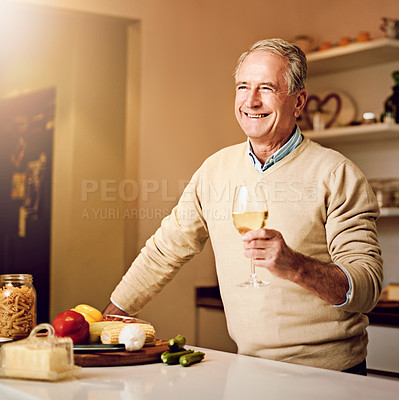 Buy stock photo Shot of a senior man enjoying a glass of wine while preparing dinner in his kitchen