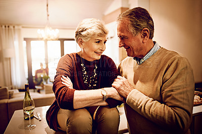 Buy stock photo Shot of an elderly couple chatting and drinking wine together in their kitchen