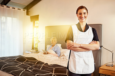 Buy stock photo Portrait of a young nurse standing with her arms folded while her patient sits in bed in the background