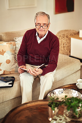 Buy stock photo Shot of a senior man working out a budget while sitting on the living room sofa