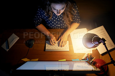 Buy stock photo High angle shot of a young businesswoman working late on a computer in an office