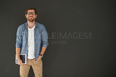 Buy stock photo Studio portrait of a young man holding his tablet against a grey background