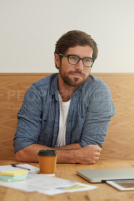 Buy stock photo Cropped shot of a young man looking thoughtful while sitting at a table