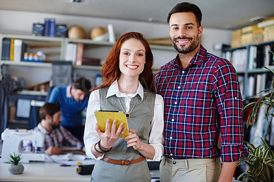 Buy stock photo Portrait of two young fashion designers standing in the workshop while their colleagues work in the background