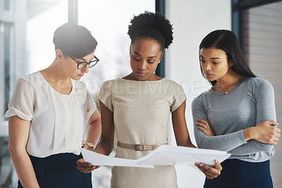 Buy stock photo Shot of a group of businesswomen analyzing paperwork together