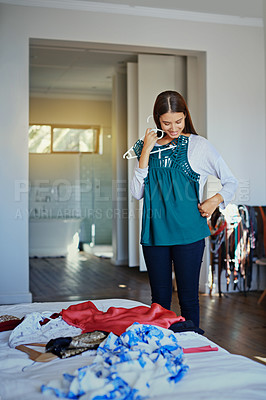 Buy stock photo Shot of a young woman standing in her bedroom choosing outfits