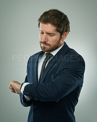 Buy stock photo Studio shot of a corporate businessman checking the time against a grey background