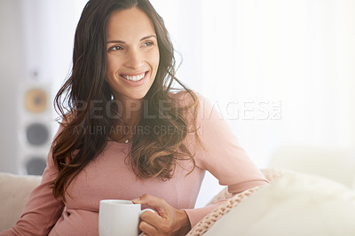 Buy stock photo Shot of a pregnant woman having a warm beverage and relaxing at home