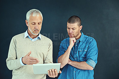 Buy stock photo Shot of a mature businessman showing his younger colleague something on a tablet in the studio