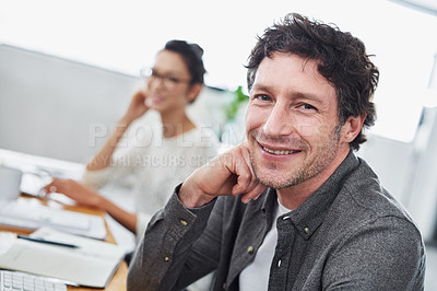 Buy stock photo Portrait of two smiling designers sitting at their workstations in an office