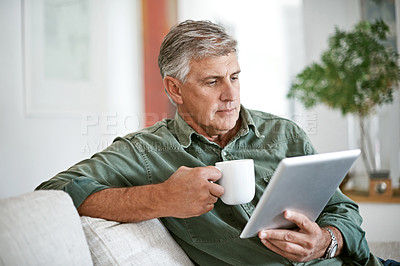 Buy stock photo Cropped shot of a mature man drinking coffee while using a digital tablet at home