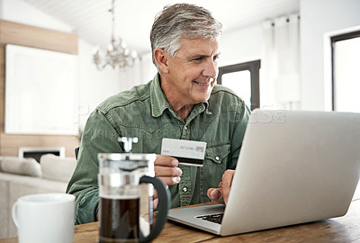 Buy stock photo Cropped shot of a mature man using a credit card to make an online payment at home