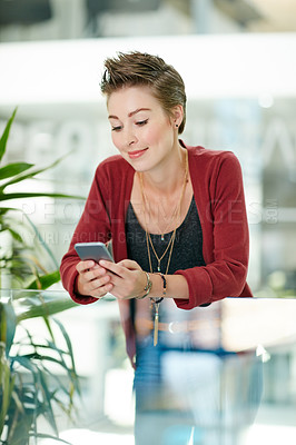 Buy stock photo Shot of an attractive young businesswoman using her cellphone in the office