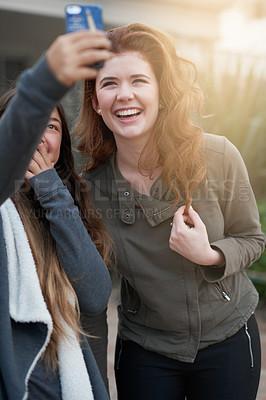 Buy stock photo Shot of two young women taking a selfie outdoors