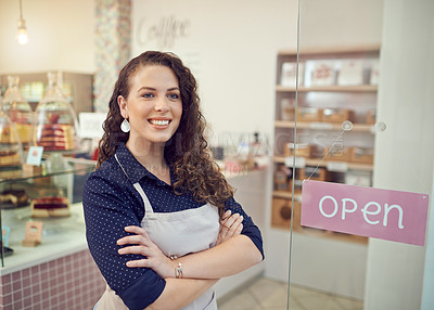 Buy stock photo Shot of a young woman standing by the door of her cake shop