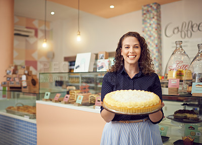 Buy stock photo Portrait of a young woman holding a large cake in her bakery
