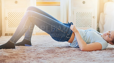 Buy stock photo Shot of a young woman struggling to fit into her jeans at home