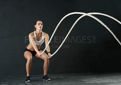 Buy stock photo Studio shot of an attractive young woman working out with heavy ropes against a dark background