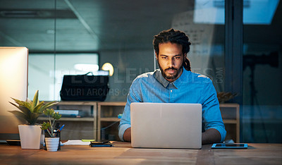 Buy stock photo Cropped shot of a young designer working late on a laptop in an office