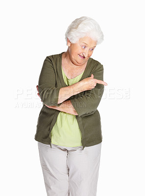 Buy stock photo Portrait of a happy senior woman pointing down isolated against white