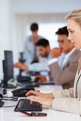 Buy stock photo Business woman working on computer with colleagues in background