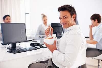 Buy stock photo Business man eating bowl of fruit salad in front of computer with colleagues in background