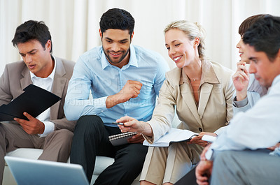 Buy stock photo Colleagues discussing project during meeting with business woman pointing at laptop
