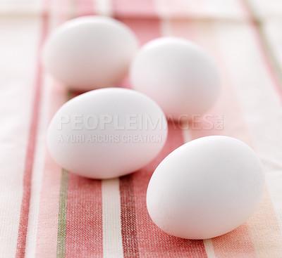Buy stock photo Closeup of four farm fresh white eggs on table cloth