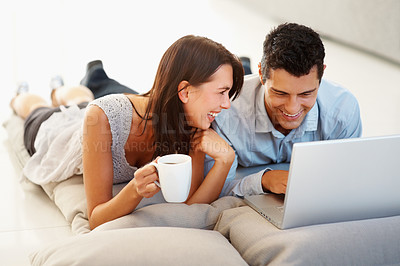 Buy stock photo Happy young woman holding coffee while man working on laptop