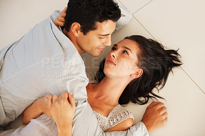 Buy stock photo Top view of young couple lying on the floor and looking at each other