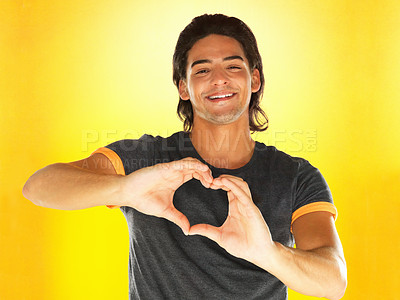 Buy stock photo Attractive man making heart sign over heart