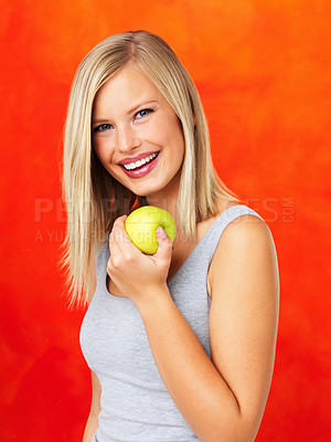 Buy stock photo Happy woman holding green apple on orange background