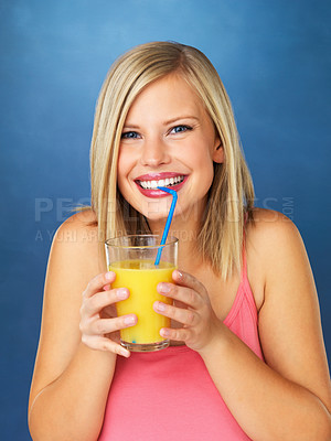 Buy stock photo Closeup of pretty woman sipping orange juice against blue background