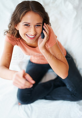 Buy stock photo Top view of happy female talking on cell phone and gesturing with pointed finger