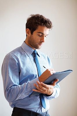 Buy stock photo Businessman with serious look writing on clipboard