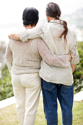 Buy stock photo Rear view of a loving senior couple standing with arms around in a park - Outdoor