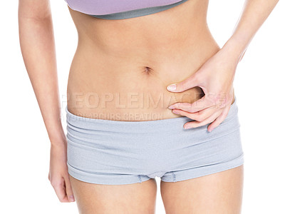 Buy stock photo Weight loss - A shot of a fit and slim girl checking her abdominal fat