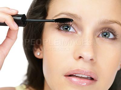 Buy stock photo Closeup portrait of a modern female applying mascara against white background