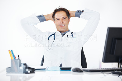 Buy stock photo Portrait of a happy middle aged doctor sitting relaxed at his desk with his arms behind his head