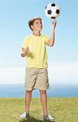 Buy stock photo Full length portrait of cute small boy balancing football on fingers - Outdoors