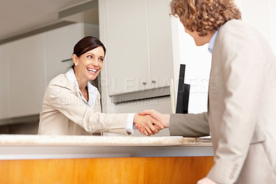 Buy stock photo Mature receptionist welcomes a businessman with a handshake and a wide smile