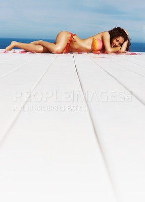 Buy stock photo Happy woman lying in a bikini on a floor with her hands on her head