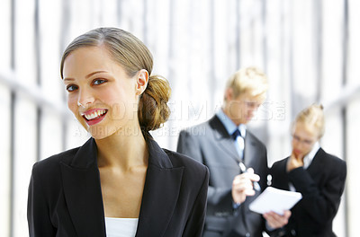 Buy stock photo Portrait of a young businesswoman with her colleagues in the background