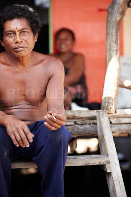 Buy stock photo A middle-aged Thai man sitting smoking on the steps to his house