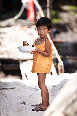 Buy stock photo Portrait of an adorable little kid from rural Thailand enjoying food