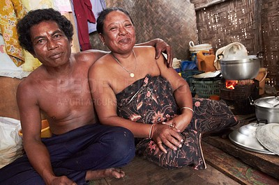 Buy stock photo A Thai husband sitting on the floor with his arm around his wife's shoulder waiting for the food to cook