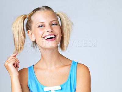 Buy stock photo Portrait of attractive young blonde in pigtails playing with her hair