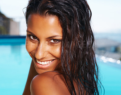 Buy stock photo Portrait of a beautiful ethnic woman grinning at you while outdoors by her pool