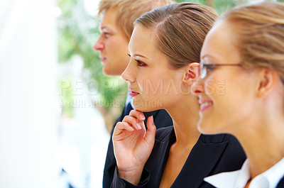Buy stock photo Cropped shot of three business colleagues sitting in a row